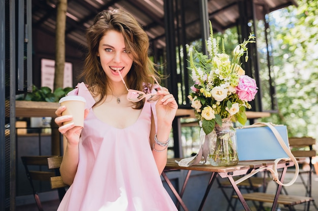 Portrait of young smiling happy pretty woman with sitting in cafe drinking coffee, summer fashion outfit, pink cotton dress, trendy apparel accessories