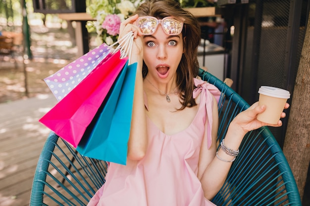 Portrait of young smiling happy pretty woman with surprised face expression sitting in cafe with shopping bags drinking coffee, summer fashion outfit, pink cotton dress, trendy apparel