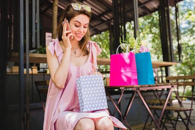 Ritratto di giovane donna graziosa felice sorridente con espressione del viso sorpreso seduto nella caffetteria con borse della spesa parlando al telefono, vestito di moda estiva, abito di cotone rosa, abbigliamento alla moda