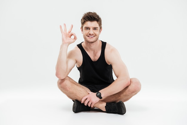 Portrait of a young smiling healthy fitness man sitting