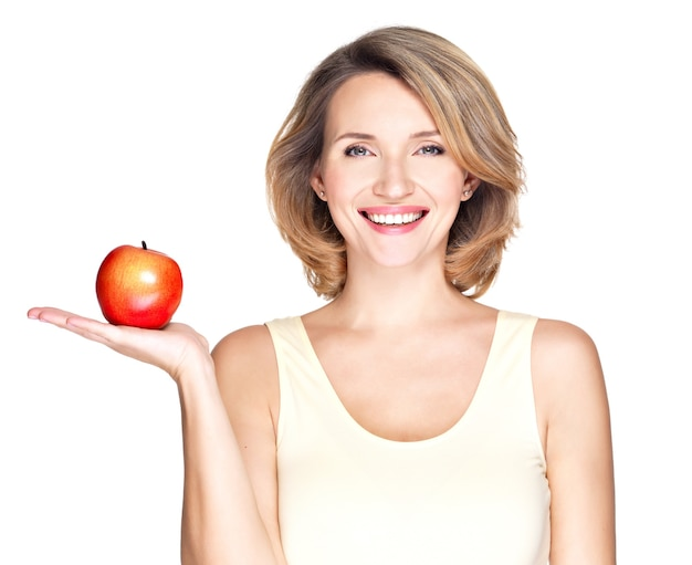 Portrait of a young smiling healthy woman with red apple isolated on white.