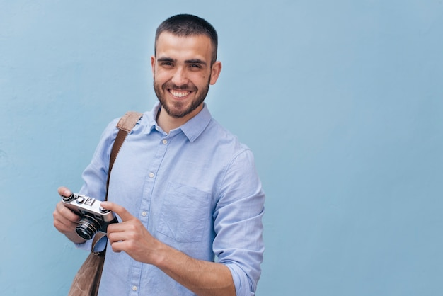 Portrait of young smiling man holding camera standing against blue wall