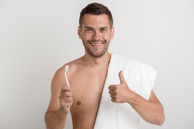 Portrait of young smiling man showing thumb up gesture while holding tooth brush