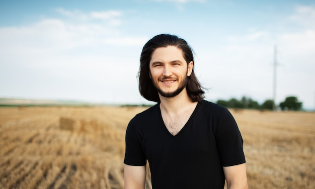 Portrait of young smiling man in wheat field.