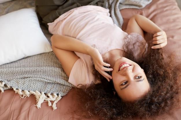 Ritratto di giovane donna sorridente piuttosto afroamericana sdraiata sul letto nella stanza di lei e parlando al telefono.