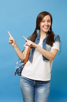 Portrait of young smiling pretty casual woman student in denim clothes with backpack pointing index fingers aside isolated on blue background. education in university. copy space for advertisement.