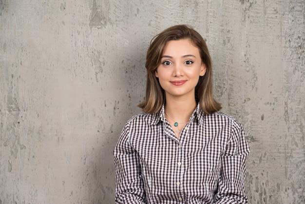 Ritratto di una giovane ragazza carina sorridente in camicia a quadri in posa