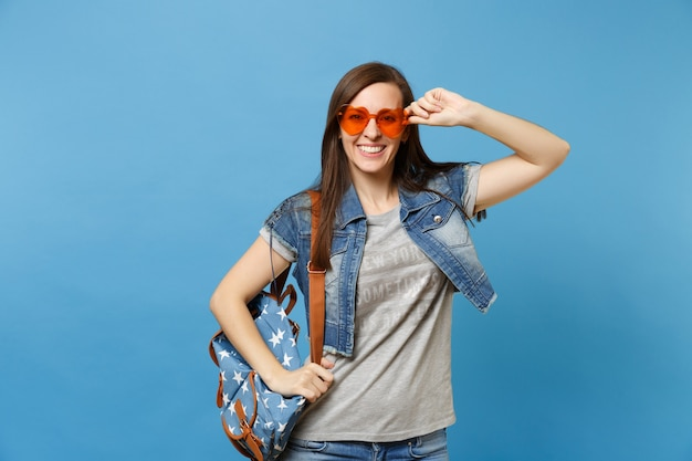 Portrait of young smiling pretty woman student in grey t-shirt denim clothes with backpack holding orange heart glasses isolated on blue background. education in college. copy space for advertisement.