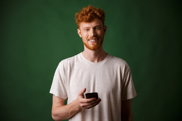 Portrait of young smiling redhead bearded young man, holding mobile phone