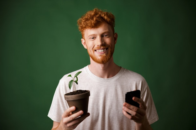 Portrait of young smiling redhead bearded young man, holding spotted plant and mobile phone
