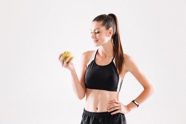 Portrait of a young smiling sportwoman holding green apple