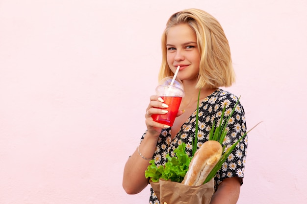 Portrait of young smiling student woman with craft shop bag, with green salad, onion and bread. healthy food, snack