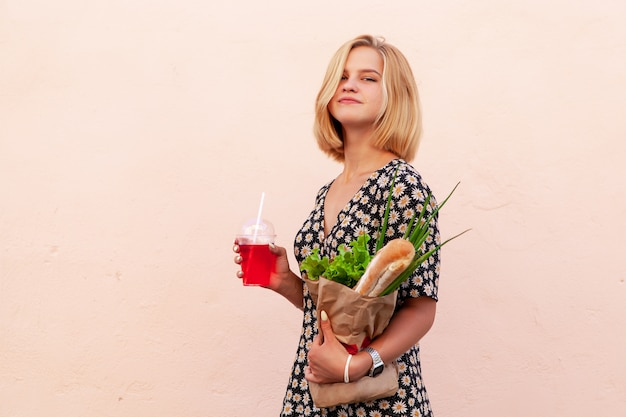 Portrait of young smiling student woman with craft shop bag, with green salad, onion and bread.  healthy food