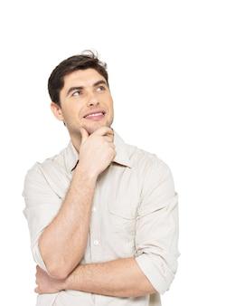 Il ritratto del giovane uomo di pensiero sorridente cerca in casuals isolato su priorità bassa bianca.