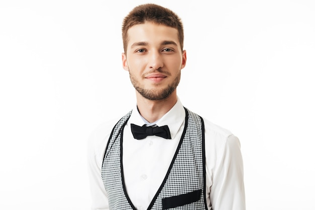 Portrait of young smiling waiter with beard in bow tie dreamily