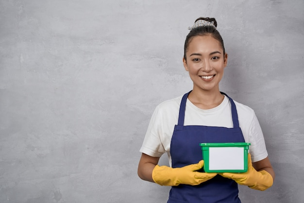 Portrait of young smiling woman cleaning lady in uniform and yellow rubber gloves holding green