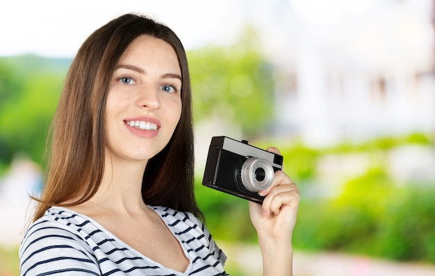 Portrait of a young smiling woman filming with retro camera isolated