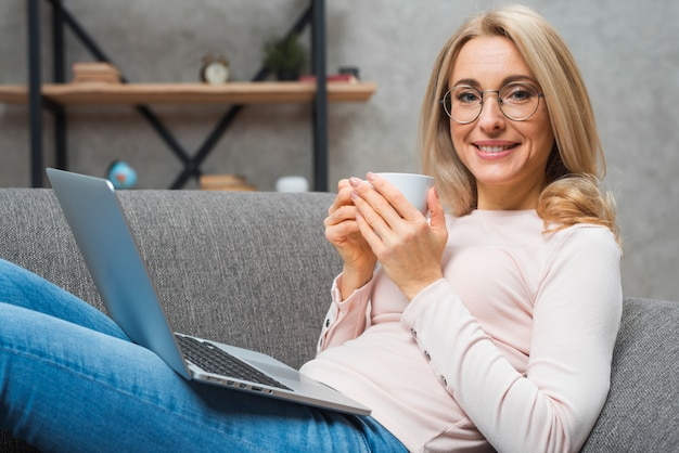 Portrait of a young smiling woman holding cup of coffee with an open laptop on her lap