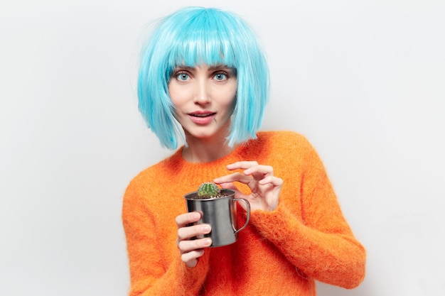 Portrait of young smiling woman holding steel mug with cactus. wearing blue wig and orange sweater.