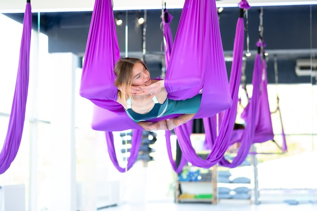 Portrait young smiling woman practice in aero stretching swing. aerial flying yoga exercises practice in purple hammock in fitness club.
