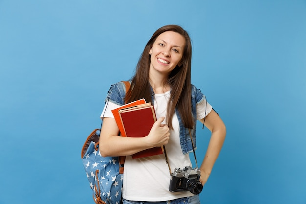 Portrait of young smiling woman student with backpack and retro vintage photo camera on neck holding school books isolated on blue background. education in high school university college concept.