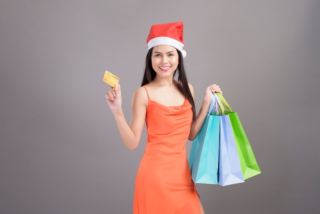 A portrait of young smiling woman wearing red santa claus hat is holding credit card and colorful shopping bag isolated gray background studio, christmas and new year concept.