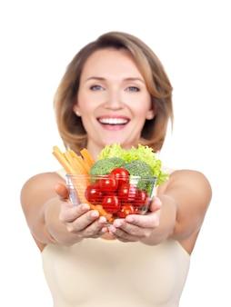 Ritratto di una giovane donna sorridente con un piatto di verdure isolato su bianco.