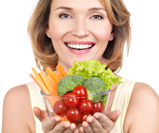 Portrait of a young smiling woman with a plate of vegetables isolated on white.