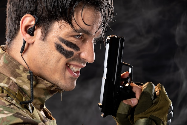 Portrait of young soldier in camouflage holding gun on black wall
