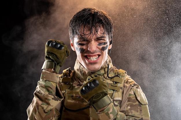 Ritratto di giovane soldato che si rallegra in uniforme sul muro scuro
