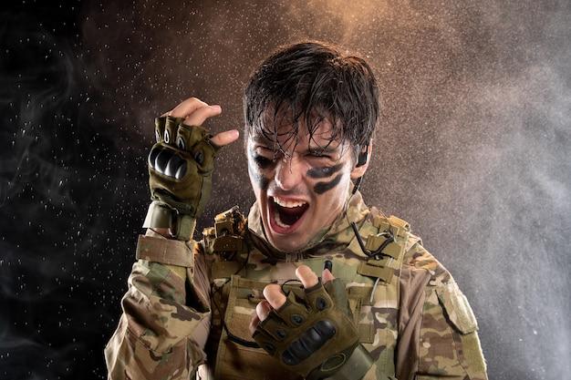 Ritratto di giovane soldato che urla in uniforme sul muro scuro