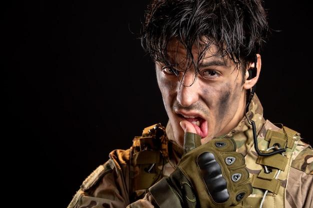 Ritratto di giovane soldato in uniforme sul muro scuro