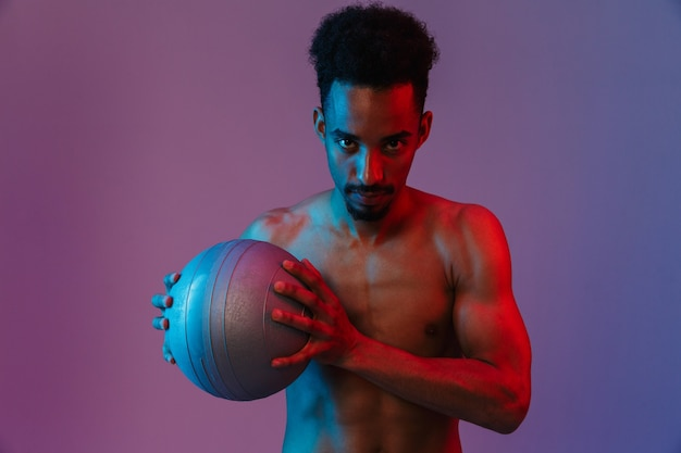 Portrait of young sporting shirtless african american man posingwith fitball isolated over violet wall