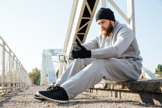 Portrait of a young sports man in hat and sports wear using mobile phone while having rest after workout outdoors