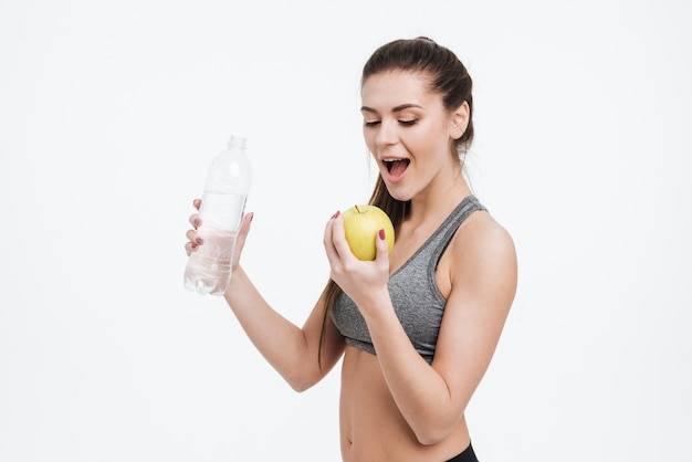 Portrait of young sports woman holding water bottle and biting apple isolated