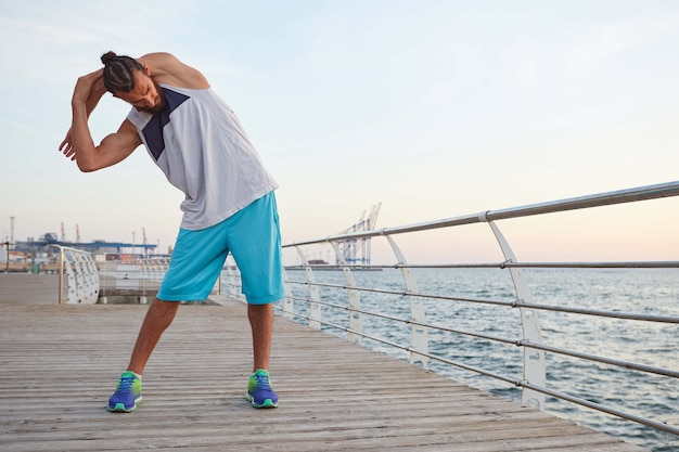 Portrait of young sporty bearded guy doing a warm-up before a morning run at the seaside, looks away.