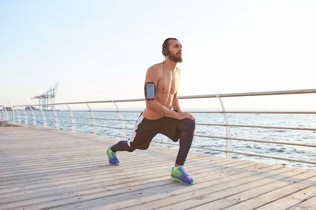 Ritratto di giovane ragazzo barbuto sportivo ascoltando le canzoni preferite in cuffia, facendo un riscaldamento prima di una corsa mattutina in riva al mare, distoglie lo sguardo.
