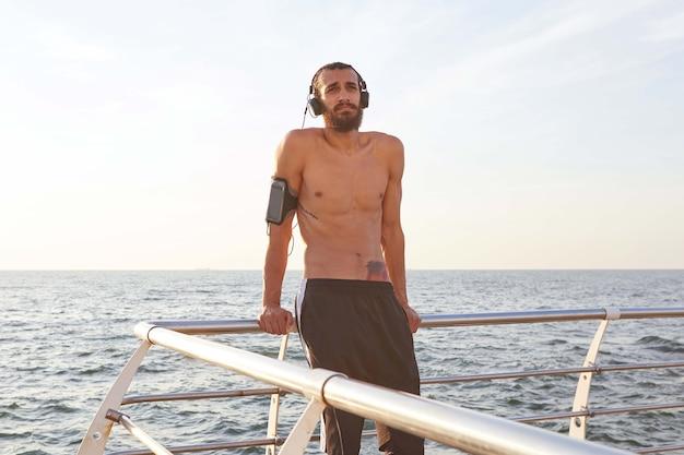 Ritratto di giovane uomo sportivo con la barba, riposo dopo aver fatto jogging in riva al mare, ascoltare la canzone preferita in cuffia. gode di una mattinata fantastica!