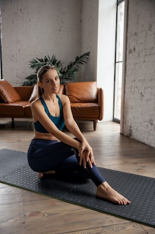Portrait of young sporty woman practicing yoga and stretching body at home. high quality photo