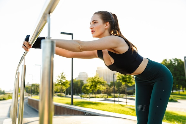 Portrait of young sporty woman wearing tracksuit leaning on railing and stretching her body during workout in green park