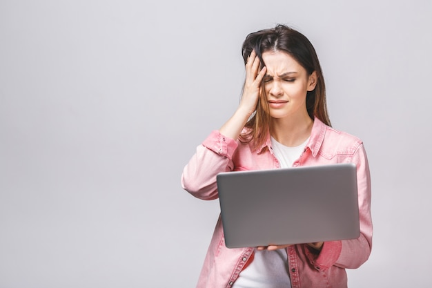 Portrait young stressed displeased worried business woman with laptop computer isolated over white background.