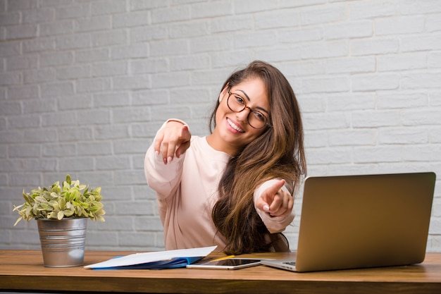 Portrait of young student latin woman sitting on her desk cheerful and smiling pointing to the front