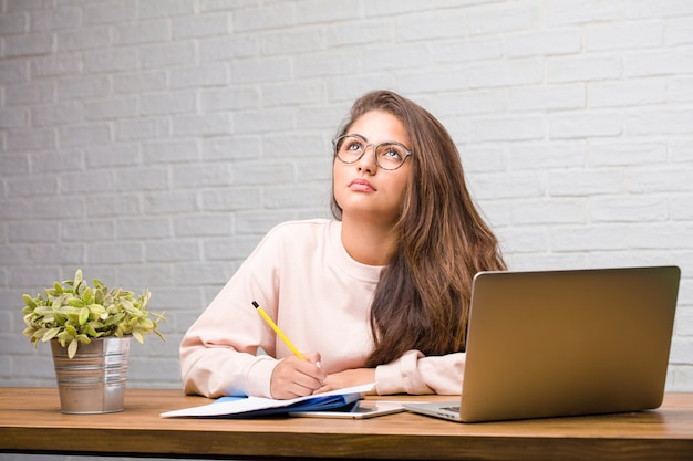 Portrait of young student latin woman sitting on her desk looking up, thinking of something fun and having an idea, concept of imagination, happy and excited