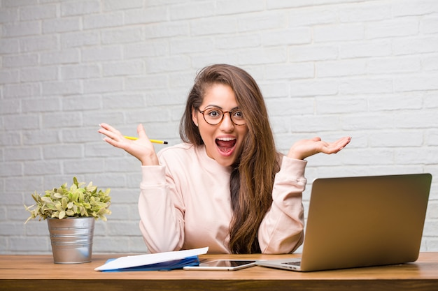 Portrait of young student latin woman sitting on her desk screaming happy, surprised by an offer or a promotion, gaping, jumping and proud
