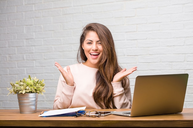 Portrait of young student latin woman sitting on her desk surprised and shocked