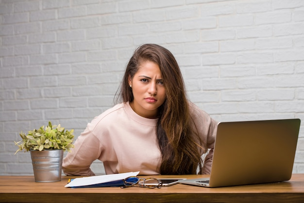 Portrait of young student latin woman sitting on her desk very angry and upset, very tense