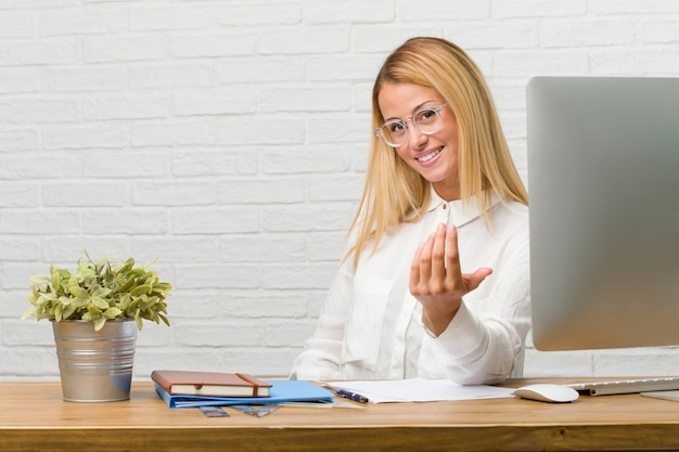 Portrait of young student sitting on her desk doing tasks inviting to come