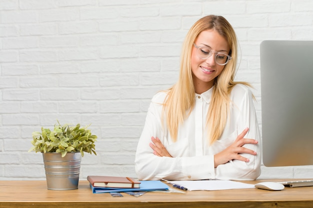 Portrait of young student sitting on her desk doing tasks looking up