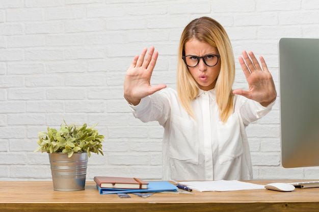 Portrait of young student sitting on her desk doing tasks serious and determined, putting hand in front, stop gesture, deny concept