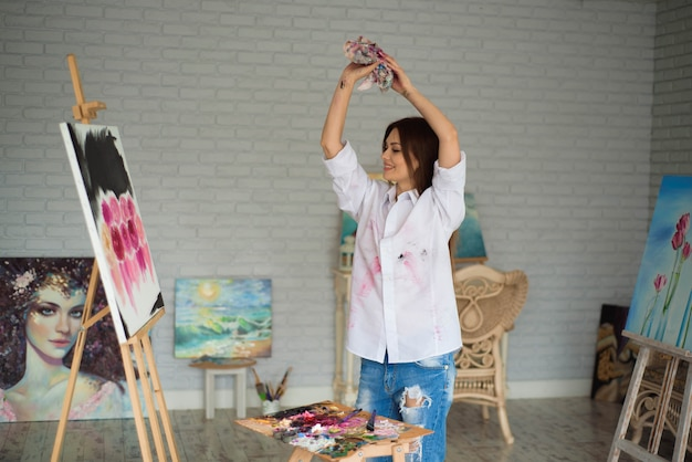 Portrait of a young student standing with painting at the studio